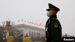 A paramilitary police officer stands guard near the Great Hall of the People before the opening session of the National People's Congress (NPC) in Beijing, China, March 5, 2021.