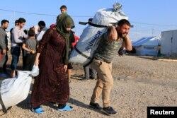 Sirijske porodice, koje su izbjegle nasilje nakon turske ofanzive u Siriji, primaju pomoć u izbjegličkom kampu Bardarash na periferiji Dohuka, Irak, 22. oktobra 2019. godine.