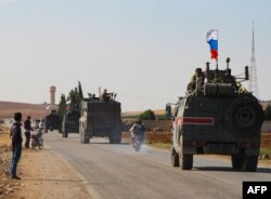 FILE - A convoy of Russian military vehicles heads for the Syrian city of Kobane, Oct. 23, 2019.