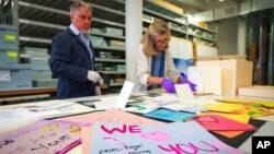 FILE - Jan Ramirez, chief curator at the 9/11 Memorial & Museum, sifts through condolence cards for a victim of 9/11 that were donated to the museum's archive, July 16, 2021, in Jersey City, N.J.