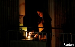 A woman lights a candle on her balcony as faithful across Italy say a prayer for people suffering from coronavirus disease (COVID-19), in Rome, March 19, 2020.