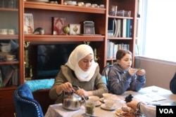 Syrian refugee Nawar Almadani sits with daughter Esraa, 10, as she plays a game. The family resettled in Chicago after living in Turkey for two years after the war in Syria broke out. (K. Khan/VOA)