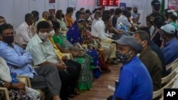 Indian's wait to receive vaccine for COVID-19 at a vaccination center in Mumbai, India, Sunday, April 18, 2021. Over 200,000 new infections were detected in the past 24 hours, and major cities, like Mumbai and New Delhi, are under virus restrictions…