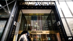 FILE - Pedestrians pass security barricades in front of Trump Tower, Feb. 17, 2021, in New York. Former President Donald Trump owns a penthouse condominium in the skyscraper and the Trump Organization has its headquarters there.