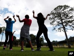 FILE - In this Sept. 24, 2019 photo, girls dance as they do exercises at a shelter for migrant teenage girls, in Lake Worth, Fla.