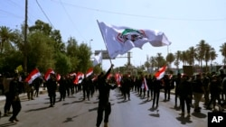 FILE - Iran-backed militia fighters march in central Baghdad, Iraq, June 29, 2021. Iraqi Shiite militias are showing a degree of defiance of their patron Iran by escalating rocket and drone attacks on the U.S. presence in the country.