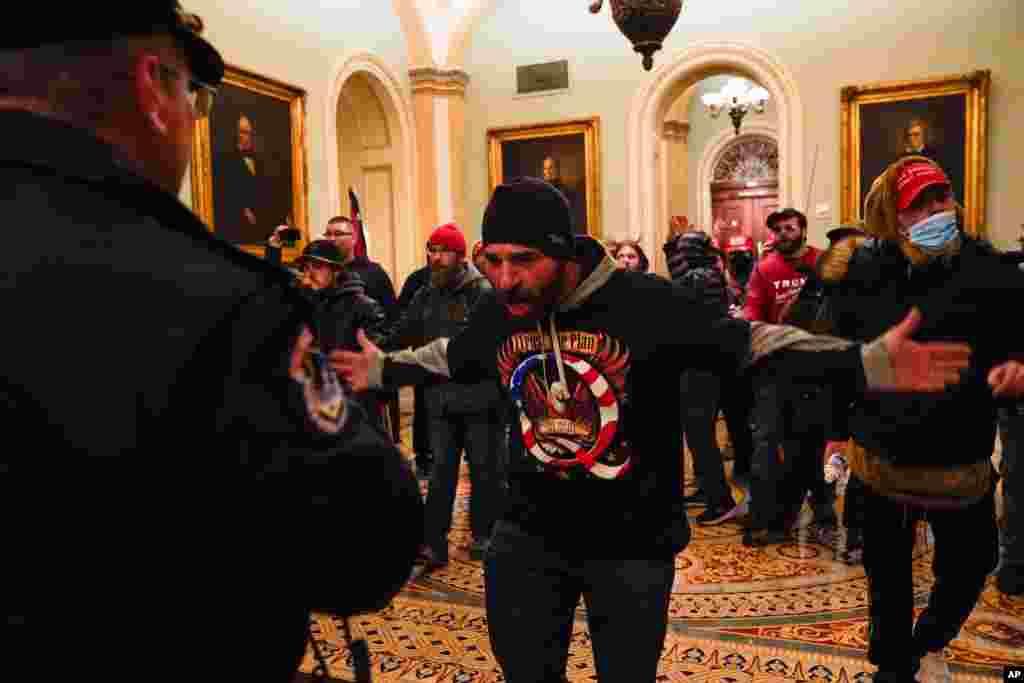 Un manifestante gesticula la policía del Capitolioen el pasillo fuera de la cámara del Senado.