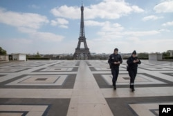 Police officers check their phones as they walk on Trocadero plaza during a nationwide confinement to counter the new coronavirus, in Paris, April 2, 2020.