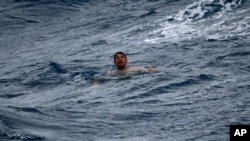 A man treads water and awaits rescue crews approximately 32 miles southeast of Key West, Fla., on July 6, 2021. The U.S. Coast Guard and a good Samaritan rescued 13 people after their boat capsized off of Key West as Tropical Storm Elsa approached.