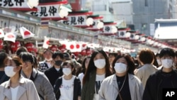 Visitors wearing face masks walk through Nakamise alley at Asakusa in Tokyo, Friday, March 20, 2020. For most people, the new coronavirus causes only mild or moderate symptoms. For some it can cause more severe illness. (AP Photo/Koji Sasahara)