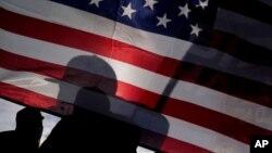 Supporters of President-elect Joe Biden and Vice President-elect Kamala Harris wave flags in Las Vegas, Nov. 7, 2020.