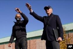 El candidato presidencial demócrata, exvicepresidente Joe Biden (der.) y el expresidente Barack Obama saludan a partidarios durante un evento de campaña en la secundaria Northwestern en Flint, Michigan, el sábado 31 de octubre de 2020.