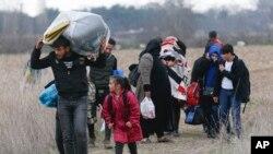 Des migrants marchent près de Pazarkule à la frontière greco-turque le 5 mars 2020.