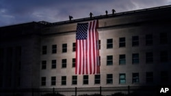 A large American flag is unfurled at the Pentagon ahead of ceremonies at the National 9/11 Pentagon Memorial to honor the 184 people killed in the 2001 terrorist attack on the Pentagon, in Washington, Friday Sept. 11, 2020. (AP Photo/J. Scott…
