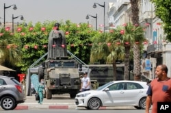 Tunisians walk past a military armored personnel carrier at Habib Bourguiba avenue in Tunis, Tunisia, July 30, 2021.