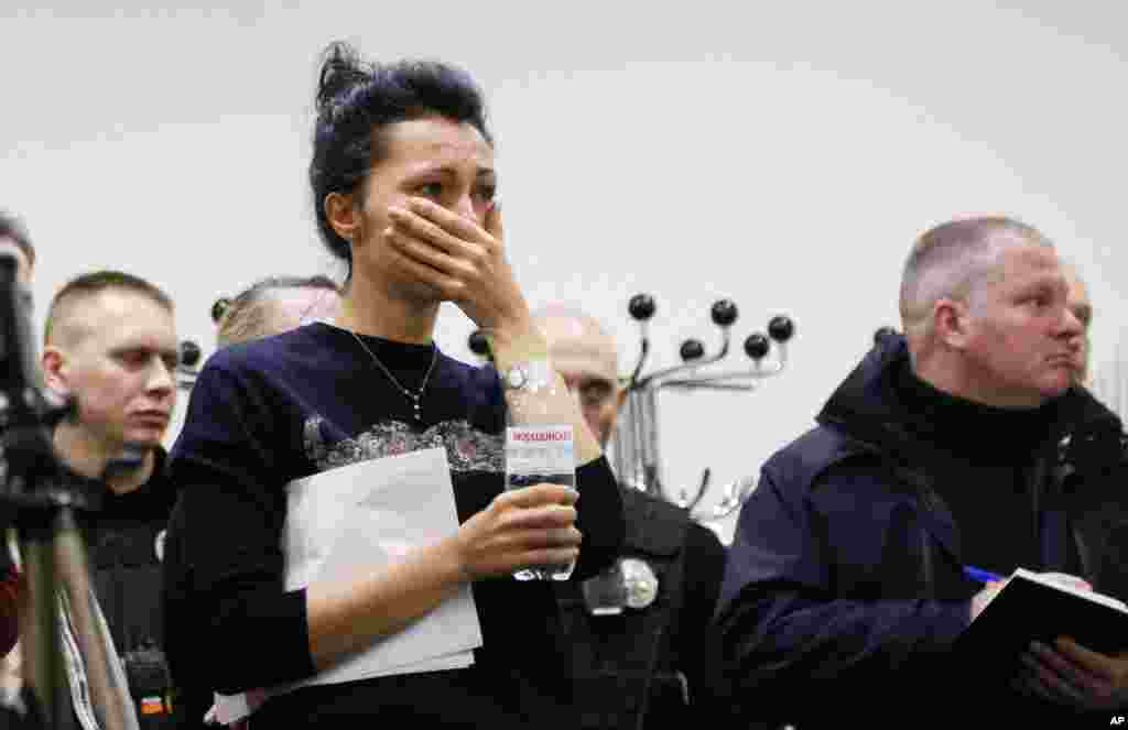 A Ukrainian International Airline company worker reacts during a briefing at Borispil international airport outside Kyiv. A Ukrainian airplane carrying 176 people crashed shortly after takeoff from Tehran's main airport, killing all onboard, Iranian state TV and officials in Ukraine said.