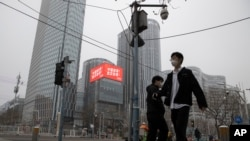 """Residents walk past a retail and office district with a screen showing propaganda which reads """"Go China! Go Wuhan"""" as businesses slowly restart in Beijing March 8, 2020."""