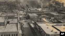 FILE - This photo provided by the Department of Special Collections, McFarlin Library, The University of Tulsa shows crowds of people watching fires during the Tulsa Race Massacre in Tulsa, Oklahoma, June 1, 1921.