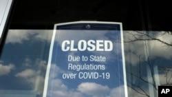 在馬薩諸塞州戴德姆的一個露天商場,一家商店的櫥窗上貼著一個關閉的告示(2020年4月22日)。