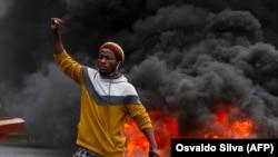 Manifestante em frente a pneus queimados na manifestação contra o governo em Luanda, 24 outubro 2020