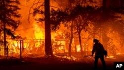 """Seorang petugas damkar melewati kobaran api dari kebakaran hutan """"Dixie Fire"""" di Plumas County, California (24/7)."""