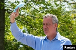 FILE - New York City Mayor Bill De Blasio speaks to people as he gives away face masks for using in public spaces to prevent the spread of coronavirus disease (COVID-19), May 16, 2020.