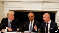 FILE - In this June 19, 2017, file photo, President Donald Trump, from left, and Satya Nadella, Chief Executive Officer of Microsoft, listen as Jeff Bezos, Chief Executive Officer of Amazon, speaks during an American Technology Council roundtable in…