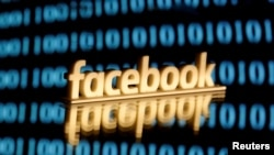 FILE PHOTO: A 3-D printed Facebook logo is seen in front of displayed binary code in this illustration picture, June 18, 2019. REUTERS/Dado Ruvic/Illustration/File Photo