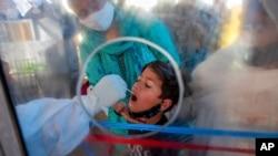 印度一位醫護人員在對一名兒童進行新冠病毒感染檢測。 (美聯社圖片)