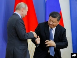 FILE - Chinese President Xi Jinping and Russian President Vladimir Putin shake hands during a ceremony at which Xi was presented with an honorary degree from St. Petersburg State University in St. Petersburg, Russia, June 6, 2019.