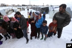 Syrian refugees wait to receive plastic cover for their tents at a refugee camp in Zahleh, Bekaa Valley, Lebanon, Jan. 8, 2015.