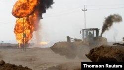 Petugas berusaha mengisolasi dan memadamkan kebakaran di sumur minyak Khabbaz, Kirkuk hari Rabu (9/12).