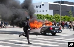 A person runs while a police vehicle is burning during a protest in Los Angeles, over the death of George Floyd, May 30, 2020.