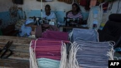 FILE - Tailors make face masks at the Tayamba Tailoring shop, which has embarked in the business of producing face masks intended to protect against the COVID-19 coronavirus, in Lilongwe, Malawi, May 4, 2020.