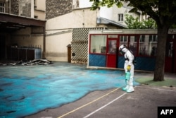 A worker sprays a gel on the ground to absorb lead during a decontamination operation at Saint Benoit school near Notre-Dame cathedral in Paris, Aug. 8, 2019.
