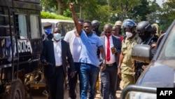 តន្ត្រីករជនជាតិអ៊ូហ្គាន់ដា ដែលបានប្រែក្លាយទៅជាអ្នកនយោបាយ លោក Robert Kyagulanyi ដែលត្រូវបានគេស្គាល់ផងដែរថា ឈ្មោះ Bobi Wine លើកដៃនៅពេលលោកដើរទៅតុលាការនៅក្រុង Ingangaកាលពីថ្ងៃទី១៩ ខែវិច្ឆិកា ឆ្នាំ២០២០។
