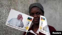 Une femme pose avec des drapeaux à l'effigie du pape François devant une église catholique à Maputo, Mozambique, le 31 août 2019.