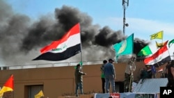 Smoke rises after pro-Iranian militiamen and their supporters set a fire in front of the U.S. embassy in Baghdad, Iraq, Jan. 1, 2020.