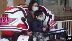 遊客在台灣台北市台北兒童遊樂園戴上口罩,以防止新的冠狀病毒傳播。 (2020年4月11日)