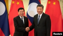FILE - Laos' Prime Minister Thongloun Sisoulith and China's President Xi Jinping shake hands before a meeting at the Great Hall of the People in Beijing, China, Jan. 6, 2020.