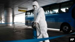 FILE - A State Commission of Quality Management staff member in protective gear disinfects a ground transportation area at the Pyongyang Airport in Pyongyang, North Korea, Feb. 1, 2020.