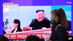 A woman passes by a TV screen showing an image of North Korean leader Kim Jong Un and his sister Kim Yo Jong during a news program at the Seoul Railway Station in Seoul, South Korea, Saturday, May 2, 2020. Kim made his first public appearance in 20…