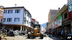 Workers clear mud from a street in Bozkurt town, Kastamonu province, Turkey, Aug. 14, 2021. The death toll from severe floods and mudslides in coastal Turkey was near 60, the country's emergency and disaster agency said.