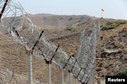 FILE - A view of the border fence outside the Kitton outpost on the border with Afghanistan, in North Waziristan, Pakistan, Oct. 18, 2017.