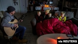 Brett Archibad, whose home was without electric power following winter weather, entertains his family as they try to stay warm in their home the BlackHawk neighborhood in Pflugerville, Texas, Feb. 16, 2021. (Ricardo B. Brazziell/via Reuters)