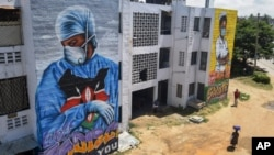 "Residents in Mombassa, Kenya, walk in front of informational murals painted on the side of an apartment block about the coronavirus and paying tribute to medical workers with the messages ""We'll Protect You"" and ""We Salute You,"" Aug. 17, 2020."