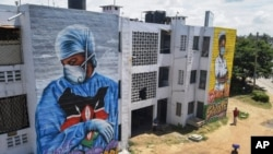 """Residents in Mombassa, Kenya, walk in front of informational murals painted on the side of an apartment block about the coronavirus and paying tribute to medical workers with the messages """"We'll Protect You"""" and """"We Salute You,"""" Aug. 17, 2020."""
