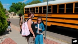 Dawn Lourenco plays with her daughter Mimi's hair after the 8-year-old got home from school on Friday, Sept. 3, 2021, in Albuquerque, N.M. Lourenco's two other children were forced to learn remotely due to outbreaks in their schools. Her daughter…