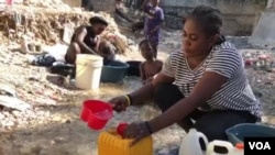 A woman mixes Clorox with water to drink in Port-au-Prince, Haiti, on April 3, 2020. Some Haitians believe the mixture can prevent them from COVID-19 infection.