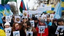 Украинские и крымско-татарские активисты держат портреты с именами жертв российской аннексии Крыма во время митинга в Киеве, 26 февраля 2017 года